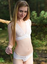 Cute blonde teen with pale skin nude by an old building